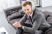 Fotografie smiling businessman in headphones sitting on couch at home