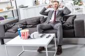 Fotografie lächelnd Geschäftsmann im Kopfhörer zu Hause sitzen und entspannen auf couch