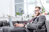 podnikatel v brýlích nošení sluchátek a používání notebooku na pohovce