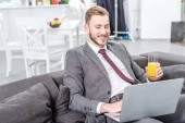 smiling businessman in formal wear drinking orange juice and using laptop