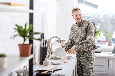Smiling army soldier cleaning dishes in kitchen stock vector