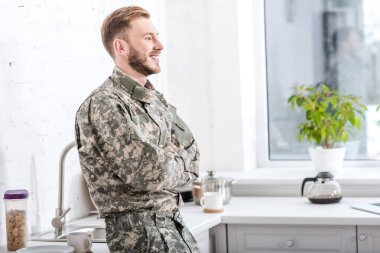 Smiling army soldier with arms crossed in kitchen stock vector
