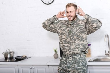 handsome soldier in military uniform wearing headphones and listening music at kitchen