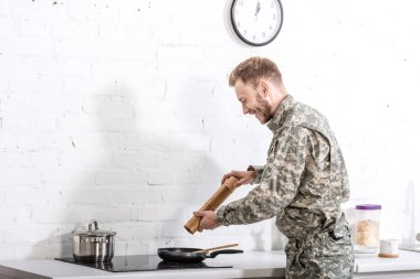 Smiling army soldier using pepper pot while cooking in kitchen stock vector