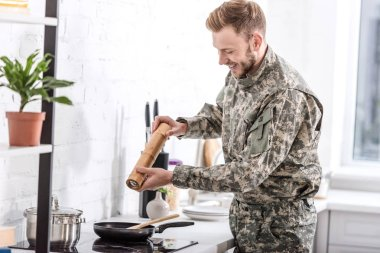 Army soldier using pepper pot while cooking in kitchen stock vector