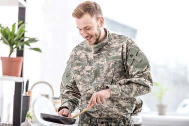 Smiling army soldier cooking on pan in kitchen stock vector