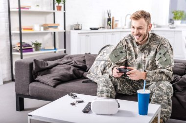 Smiling army soldier sitting on couch at home and playing video game stock vector