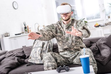 army soldier touching air during vr experience on couch