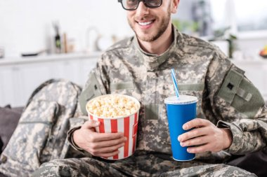 Smiling soldier in 3d glasses watching movie with popcorn and soda water stock vector