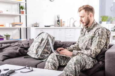 Focused army soldier using laptop on couch at home stock vector