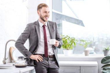 handsome businessman drinking coffee in kitchen at home