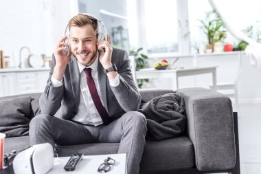 smiling handsome businessman in headphones sitting on couch at home