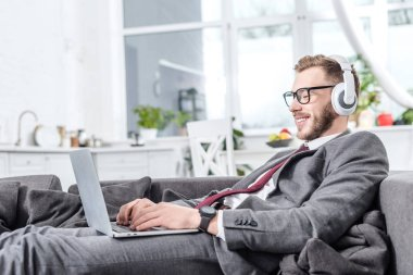 businessman in glasses wearing headphones and using laptop on couch