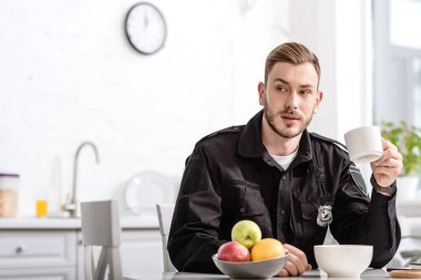 handsome policeman at kitchen sitting, holding cup of hot coffee and having breakfast at kitchen table