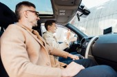 Fotografie side view of smiling handsome father teaching teen son driving car