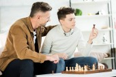 father hugging teen son while he looking at chess figure at home