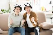 Fényképek izgatott apa és tini fiú Labdarúgás kalap játék figyeli és sikoltozik a kanapén, otthon