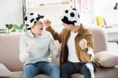 Fényképek izgatott apa és tini fiú Labdarúgás kalap játék figyeli és sikoltozik a kanapé otthon, néztek egymásra