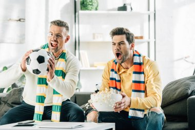 excited son and father with scarfs watching football and screaming at home