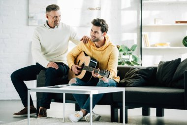 happy son playing acoustic guitar for mature father on weekend at home