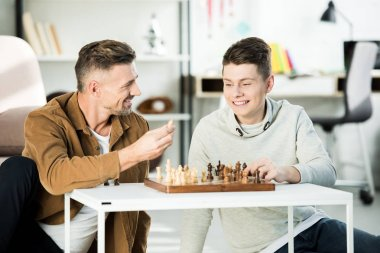 smiling father showing chess figure to teen son while playing chess at home
