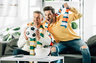 excited son and mature father with scarfs watching football and screaming at home