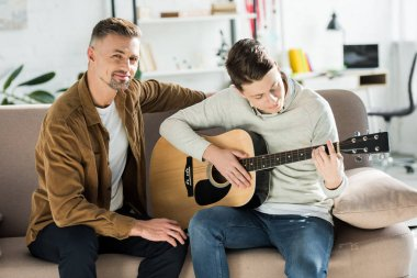 teen son playing acoustic guitar for father at home
