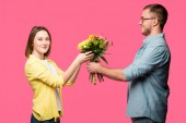 Fotografie happy young man presenting bouquet of flowers to smiling woman isolated on pink