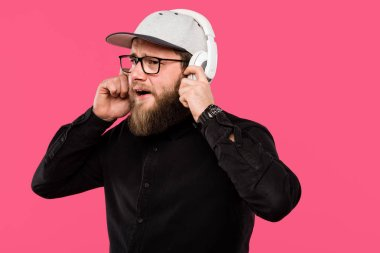 bearded male hipster listening music in headphones isolated on pink