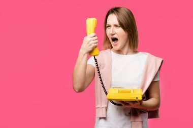 Angry young woman yelling at handset isolated on pink stock vector