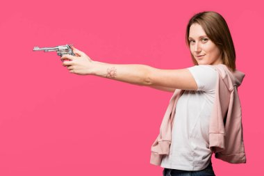 Side view of young woman holding revolver and smiling at camera isolated on pink stock vector