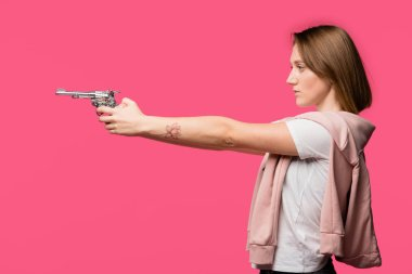 Side view of young woman holding revolver and looking away isolated on pink stock vector