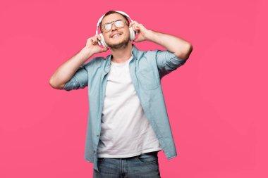 Gözlük pink izole kulaklık müzik dinlerken mutlu genç adam