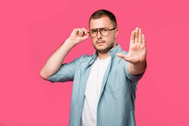 serious man adjusting eyeglasses and showing no sign isolated on pink