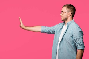 side view of man gesturing no with hand and looking away isolated on pink