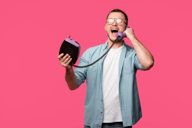 excited young man in eyeglasses talking by vintage telephone isolated on pink