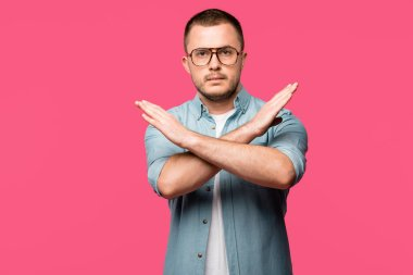 young man gesturing no with crossed arms and looking at camera isolated on pink