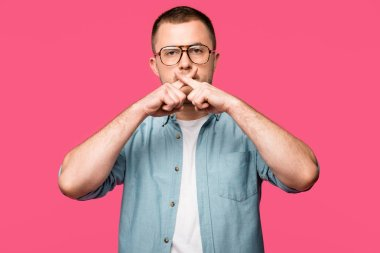 young man in eyeglasses gesturing for silence and holding crossed fingers near lips isolated on pink