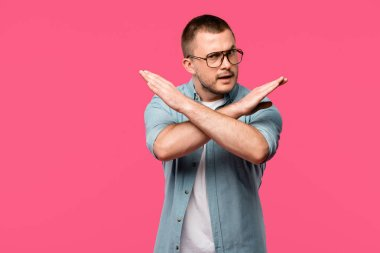 young man in eyeglasses gesturing no with crossed arms and looking at camera isolated on pink