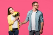 Fotografie smiling young woman holding bouquet of flowers while standing in handcuffs with man looking away isolated on pink