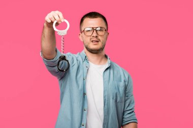 young man in eyeglasses holding handcuffs and looking at camera isolated on pink
