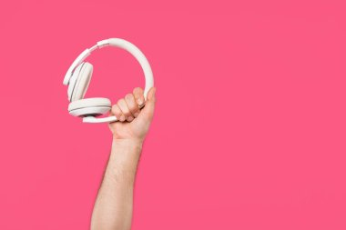 cropped shot of man holding white headphones isolated on pink