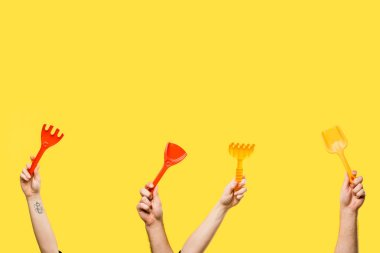 cropped shot of male and female hands holding red and yellow plastic shovels and rakes isolated on yellow