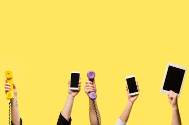 cropped shot of hands holding smartphones, digital tablet and handsets isolated on yellow