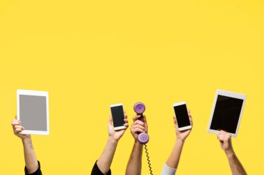 Cropped shot of hands holding smartphones, digital tablets and handset isolated on yellow stock vector