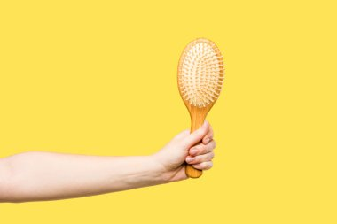 cropped shot of person holding hairbrush isolated on yellow