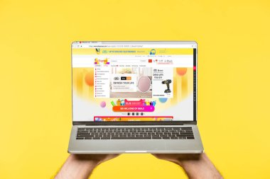 Cropped shot of person holding laptop with aliexpress website on screen isolated on yellow stock vector