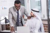 Fotografie African american businessman looking at laptop and standing near arabian partner