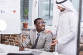 Fotografie African american businessman holding pen and looking at arabian partner in office