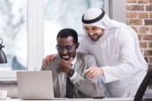 Multiethnic businessmen looking at laptop and smiling in office